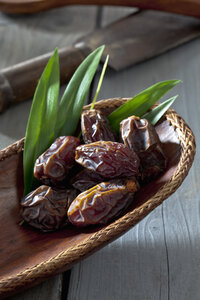 Wooden bowl with dates on wooden table - CSF020484