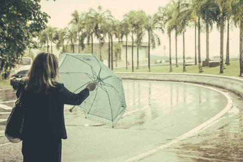 Brazil, Sao Paulo, Woman with umbrella getting prepared to get in the rain - AMC000026
