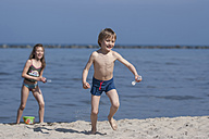 Germany, Mecklenburg-Western Pomerania, Rugia, Sellin, boy and girl playing at seashore - PA000157