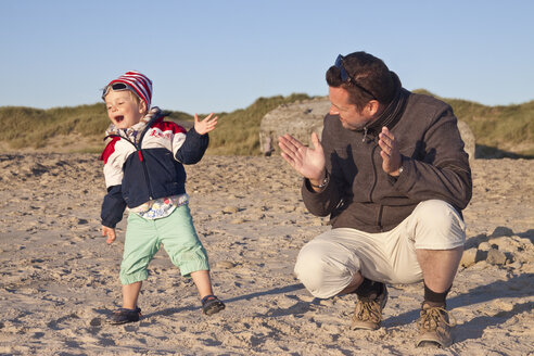 Denmark, Blavand, little girl and her father on the beach - JFEF000253