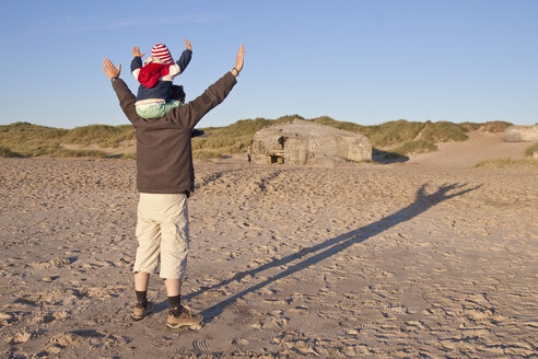 Denmark, Blavand, little girl and her father playing on the beach - JFEF000254
