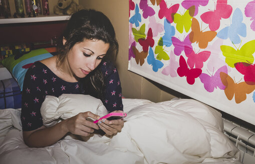 Spain, Madrid, young woman sitting on bed and using smart phone - AMCF000030