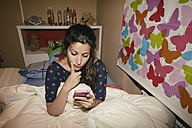 Spain, Madrid, young woman sitting on bed and using smart phone - AMCF000033