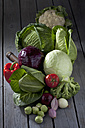 Cabbage varieties and other vegetables on grey wooden table - CSF020583