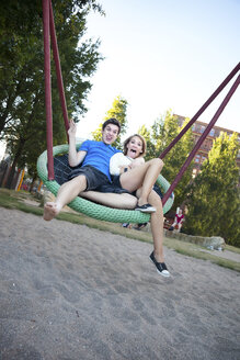 Teenage couple swinging at playground - MVC000043