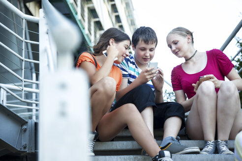 Teenage friends using mobile devices on stairs - MVC000046
