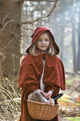 Portrait of little girl masquerade as Red Riding Hood standing in the wood - CLPF000042