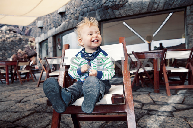 Spain, Lanzarote, laughing little boy sitting on a terrace of a restaurant - MFF000693
