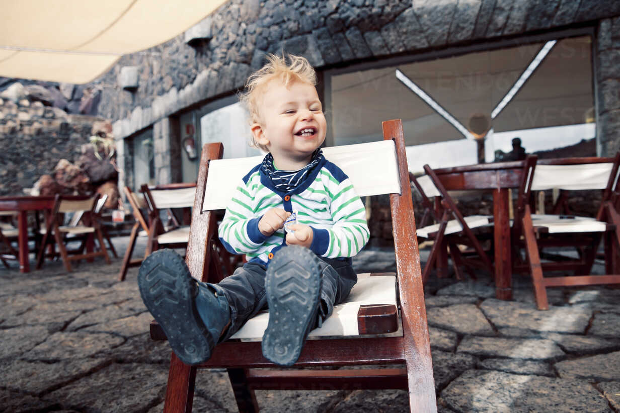 Spain, Lanzarote, laughing little boy sitting on a terrace of a restaurant - MFF000693 - Mareen Fischinger/Westend61