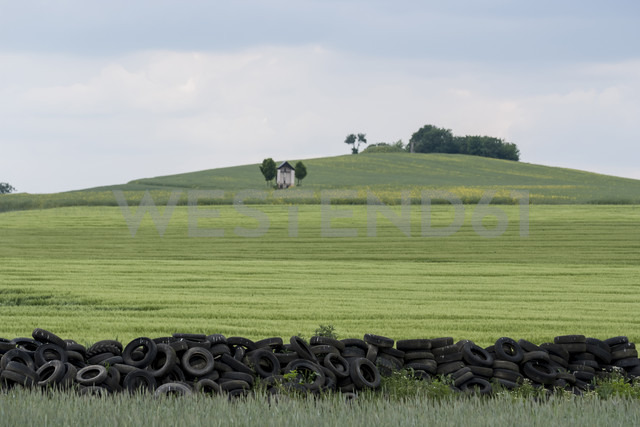 Germany, Rhineland-Palatinate, Eifel, Field landscape with old car tyres - PAF000100
