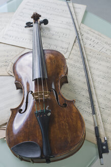 Antique violin and violin bow lying on musical notes - CRF002545