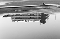Germany, North Rhine-Westphalia, Aachen, Europaplatz, part of high-rise building reflecting at puddle - HL000304