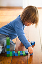 Little girl playing with blue aund green wooden building bricks - LVF000396