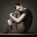 Young woman with black tights hugging her knees - CvK000013