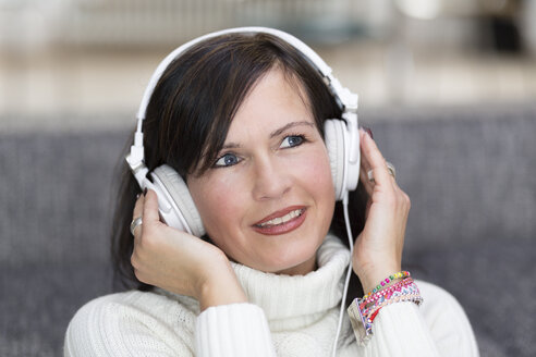 Portrait of smiling woman with white headphones hearing music - DR000339