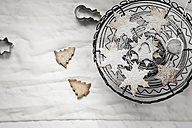 With powdered sugar sprinkled Christmas cookies, cake stand, strainer and cookie cutter on white ground - SBDF000357