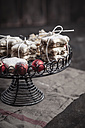 With powdered sugar sprinkled star-shaped cinnamon cookies and red Christmas baubles on cake stand - SBDF000374