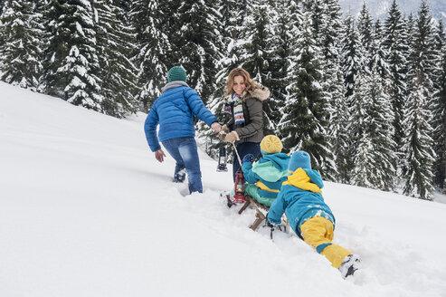 Austria, Salzburg Country, Altenmarkt-Zauchensee, Family walking in snow, pulling sledge - HHF004668