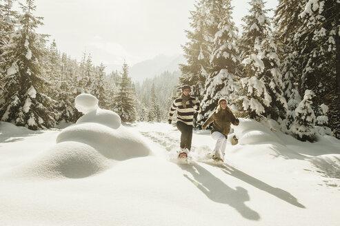 Austria, Salzburg State, Altenmarkt-Zauchensee, Couple snowshoeing in winter landscape - HHF004689