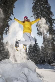 Austria, Salzburg State, Altenmarkt-Zauchensee, Woman with snowshoes jumping in winter landscape - HHF004694