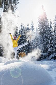Austria, Salzburg State, Altenmarkt-Zauchensee, Woman with snowshoes jumping in winter landscape - HHF004695