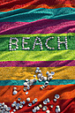 The word 'beach' formed by shells lying on a multicolored bath towel - ASF005263