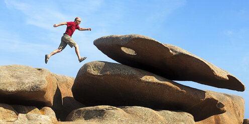 France, Bretagne, Tregastel, Man jumping on rocks - BIF000220