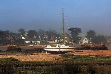 France, Bretagne, Perros-Guirec, Sailing boat in harbor at low tide - BI000224