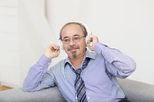 Germany, Senior man wearing head phones - DR000345