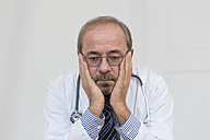 Germany, Worried doctor, head in hands - DR000343