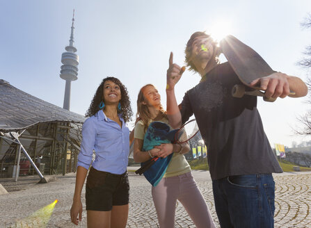 Germany, Bavaria, Munich, Three friends having fun at the Olympic Park - HSI000291
