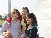 Germany, Bavaria, Munich, Three friends having fun at the Olympic Park - HSI000304