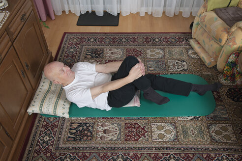 Old man making exercises in his living room - LAF000375