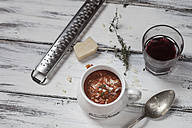 Tomato soup with parmesan, red wine, parmesan cheese with grater, thyme on wooden table - SBDF000401