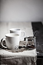 Two white mugs, wire whisk and a glass with cocoa on wooden table - SBDF000400