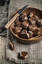 Chestnuts in wooden bowl, knife on top - SBDF000389