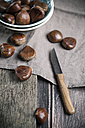 Chestnuts on wooden table and in a bowl - SBDF000387