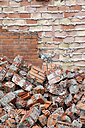 Spain, Catalonia, building site, heap of bricks at wall - JMF000278