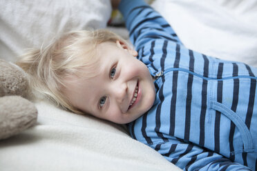 Portrait of smiling little boy lying on blanket - RBF001610