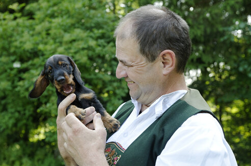Germany, Bavaria, Upper Bavaria, man in bavarian costum with young Dachshund - LB000456