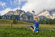 Italy, Province of Belluno, Veneto, Cortina d'Ampezzo, laughing little boy holding camera - MJF000446