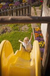 Italy, Dolomite Alps, little boy sliding on yellow slide in a garden - MJ000450