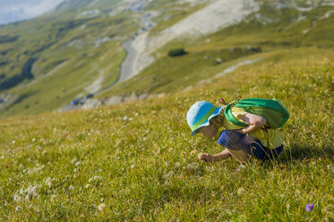 Italy, Province of Belluno, Veneto, Auronzo di Cadore, little boy crouching on alpine meadow near Tre Cime di Lavaredo - MJF000467