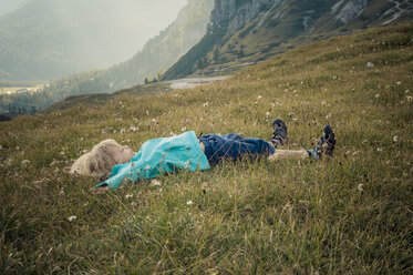 Italy, Province of Belluno, Veneto, Auronzo di Cadore, little boy lying on alpine meadow near Tre Cime di Lavaredo - MJF000468