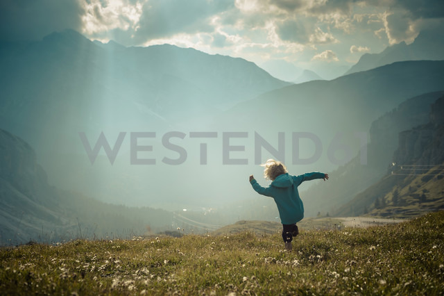Italy, Province of Belluno, Veneto, Auronzo di Cadore, little boy walking on alpine meadow near Tre Cime di Lavaredo - MJF000472