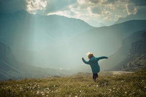 Italy, Province of Belluno, Veneto, Auronzo di Cadore, little boy walking on alpine meadow near Tre Cime di Lavaredo - MJF000472