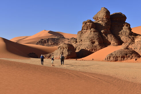 Algeria, Sahara, Tassili N'Ajjer National Park, Tadrart, people hiking between rocks and dunes of Tin Merzouga - ES000859