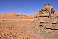 Algeria, Sahara, Tassili N'Ajjer National Park, Woman standing on rock in Tin Merzouga - ES000889