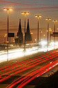 Germany, North Rhine-Westphalia, Cologne Cathedral and road traffic on lighted Zoobruecke at dusk - JAT000525