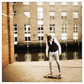 dark hair european boy with skateboard near the fleet, Germany, Hamburg - SEF000300